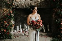 a chic strapless lace sheath wedding dress with a train and carrying a red and pink wedding bouquet
