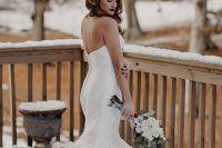 a classic strapless mermaid wedding dress and a shiny hairpiece on one side for a modern sexy bride