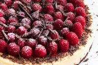 a dark chocolate raspberry cheesecake with a creamy, dark chocolate crust, topped with raspberry sauce, fresh raspberries and chocolate shavings