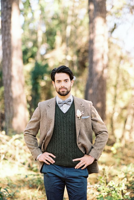 a fall groom's outfit with a grey shirt, a plaid bow, hunter green cable knit jumper, a brown tweed blazer and navy pants