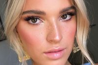 a glam look with a glossy pink lip, brown smokeys and extended eyelashes, pink blush and highlighted skin