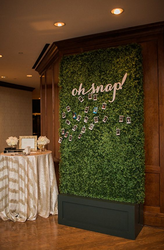 a greenery wall and Polaroids attached is a fresh new way to create your wedding guest book and make it very modern