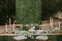 a greenery wall dotted with veyr small blooms is a stylish and bold wedding backdrop idea to rock