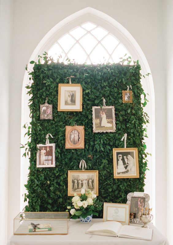 a greenery wall used to display family photos is a lovely and refined idea to rock at the wedding