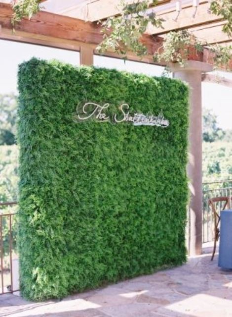 a greenery wall with a calligraphy neon sign is a stylish wedding backdrop idea to rock, it's fresh and modern