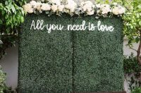 a greenery wall with a neon sign and some neutral blooms on top is a classic wedding ceremony backdrop to rock