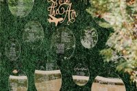 a greenery wall with an acrylic seating chart and some bold blooms on top is a very chic and bold idea for a wedding