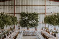 a greenery wall with calliraphy and overhead greenery installations that match create a fresh ambiencein the industrial venue