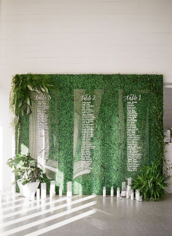 a greenery wall with ferns and foliage, candles and an acrylic seating chart is a very stylish idea for a modern wedding