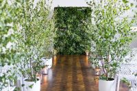 a living greenery wall and potted trees turn the indoor ceremony space into a forest