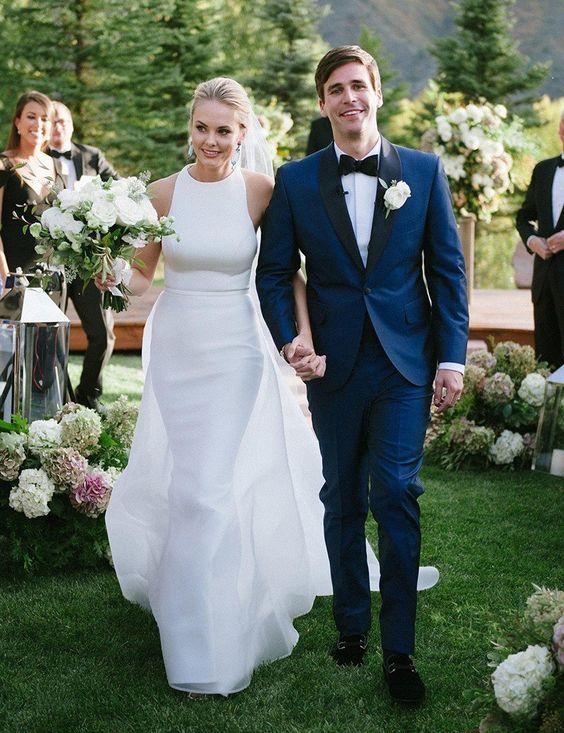 a modern plain wedding dress with a halter neckline and a sheath skirt plus an overskirt with a train