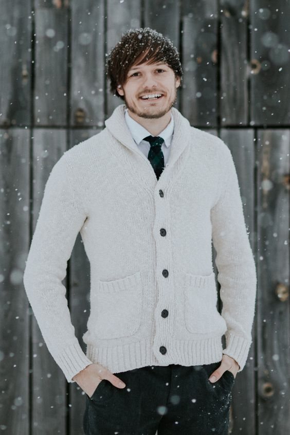 a monochromatic outfit with a white shirt, grey pants, a creamy cardigan and a tartan tie for a Christmas wedding