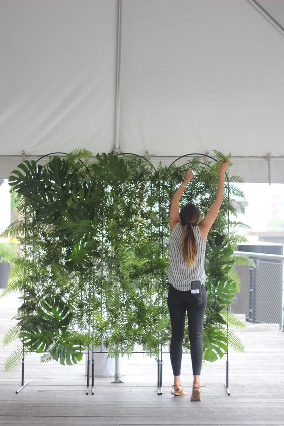 a monstera leaf and fern greenery wall is a lovely modern wedding backdrop to rock, it will look wild and fresh