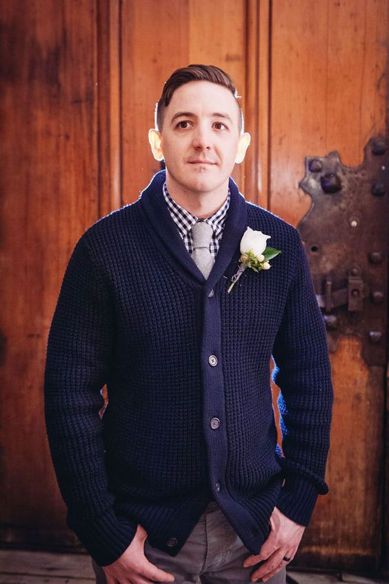 a navy gingham shirt under thick navy shawl cardigan and neutral pants for a mountain lodge wedding