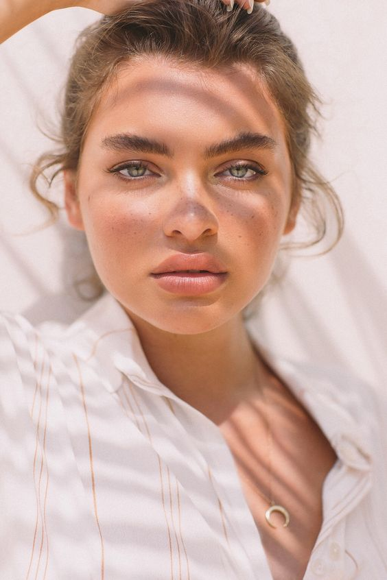 a nude makeup with a nude matte lip, slightly accented eyes and eyebrows, a touch of blush and highlights