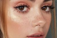 a pink makeup with a glossy pink lip, pink smokeys, extended eyelashes, blush and bronzer plus edgy eyebrows