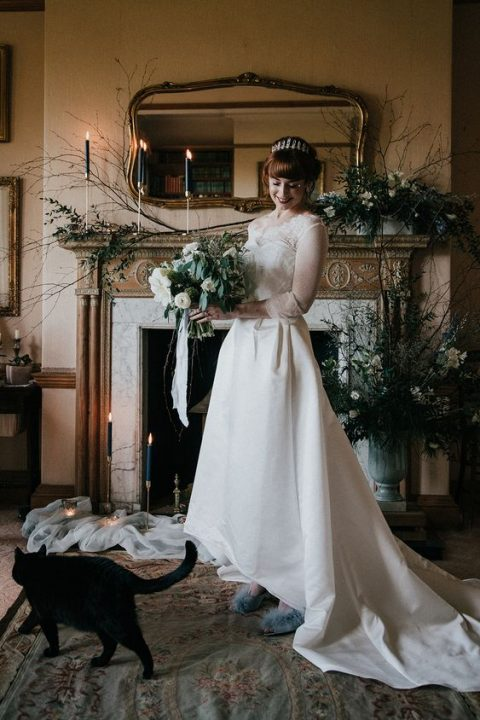a romantic A line wedding dress with a lace bodice, illusion sleeves and a neckline plus a high low skirt with a train