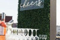 a simple boxwood wall with a neon sign will accent your wedding bar or dessert station and will make it more modern and chic