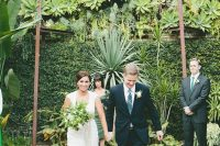 a super lush greenery wall, lots of statement plants around and succulents for a strong tropical feel at the wedding