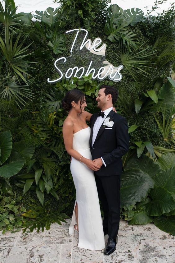 a super lush tropical foliage wall with a neon sign is a lovely idea for a modern or minimalist tropical wedding