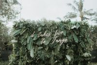 a super lush tropical leaf wall with calligraphy and candles around is a lovely modern wedding idea to rock