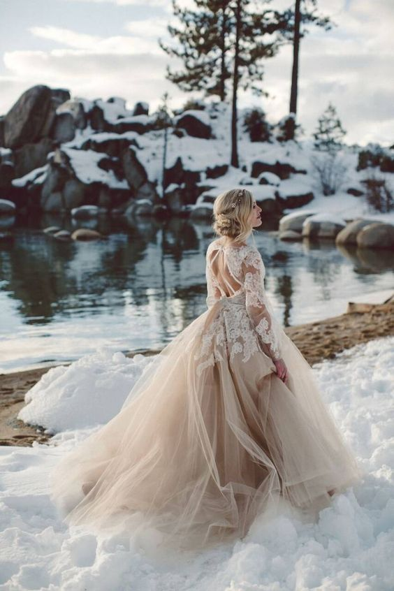 a tan wedding ballgown with white lace appliques and a tiered skirt with a train stands out in the snow