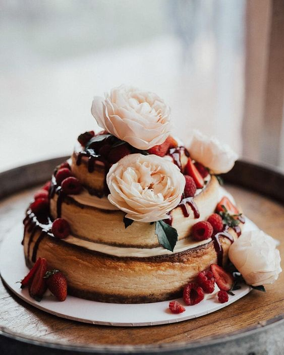 a two-stacked cheesecake topped with flowers and berries looks cute and rustic