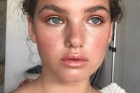a very fresh and shiny makeup with a glossy nude lip, blush, pink eyeshadow and trendy eyebrows plus highlighted skin