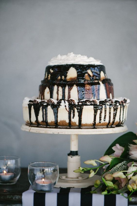 a wedding cheesecake with chocolate drip and cream on top is a delicious decadent wedding dessert