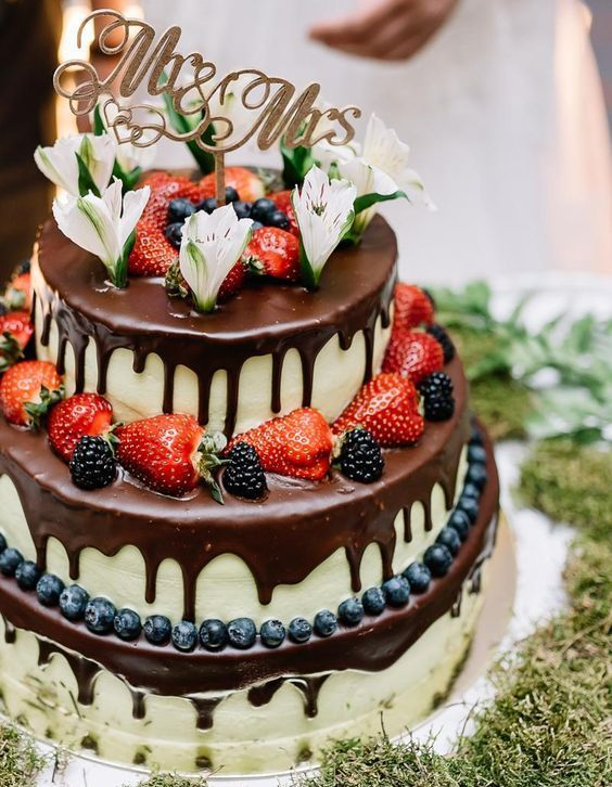 a wedding cheesecake with fresh blueberries, strawberries, blackberries chocolate drip, fresh blooms and a topper