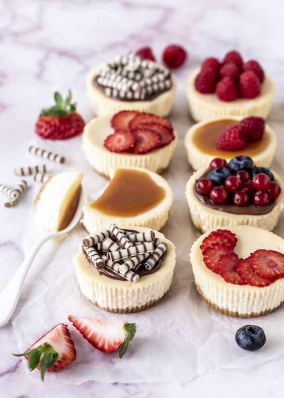 an assortment of mini cheesecakes with fresh berries and berry slices, salted caramel and mini chocolate bites
