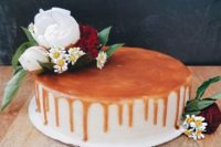 an earl grey cheesecake with salty dark caramel is topped with white peonies, green mist, red carnations, and chamomile flowers