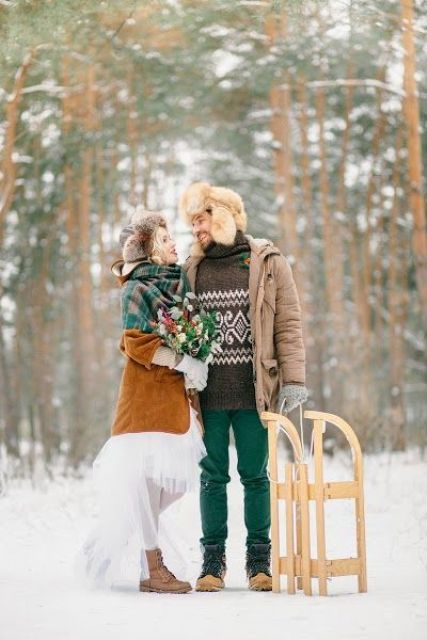 an outdoor groom's look with a brown printed sweater, emerald jeans, mustard boots, a brown puffer jacket and a fux hat