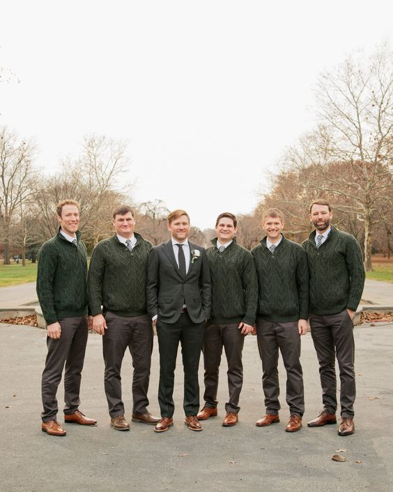 groomsmen wearing grey pants, white shirts, grey ties, green cable knit cardigans and brown shoes at a casual fall wedding