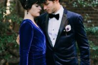 a Goth-inspired groom's look with a midnight blue velvet tux with black lapels, a black bow tie and pants and a calla boutonniere