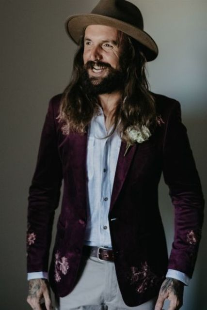 a boho groom's look with a purple floral print blazer, white jeans, an off white shirt and a hat for a fall wedding