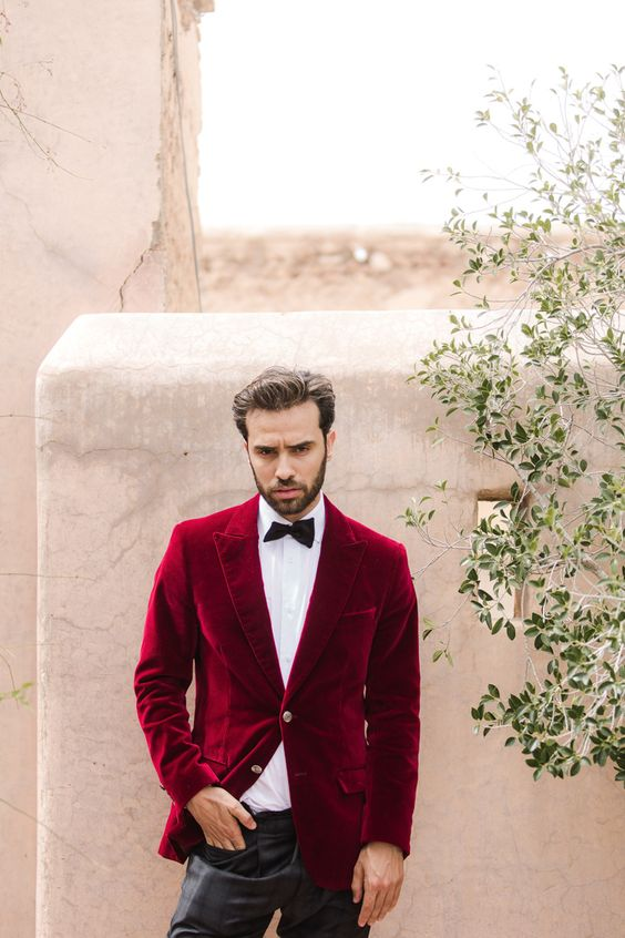 a bold and cool groom's look with a crimson velvet blazer, a white shirt, a black bow tie and grey plaid pants