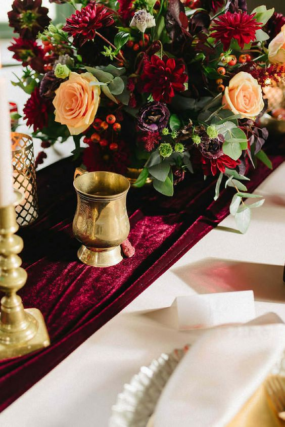 a bold and refined wedding tablescape with a marsala velvet runner and bold marsala blooms and berries is amazing for fall