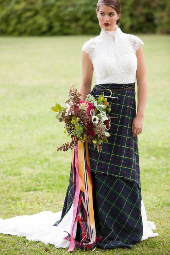 a bold bridal look with a lace A-line wedding dress with a high neckline and cap sleeves and a tartan wrap