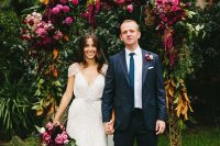 a bold floral wedding arch with plenty of greenery, pink, marsala and red blooms and magnolia leaves is veyr catchy