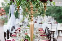 a bold summer wedding tablescape with gold chargers, candelabras with marsala blooms and pink ones plus marsala napkins