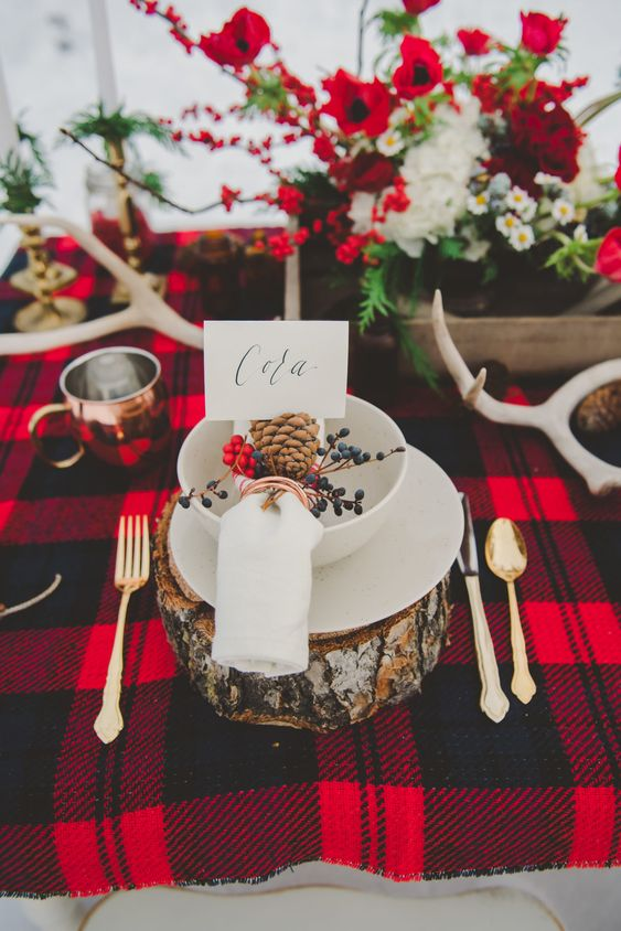 a bold winter rustic wedding tablescape with stumps, a red plaid tablecloth, red and white blooms and antlers