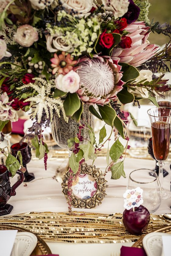 a bright and glam wedding tablescape with a gold sequin runner, marsala glasses and apples, blooms and drinks