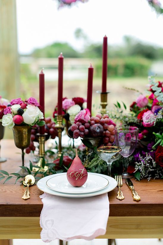 a bright and lush fall wedding tablescape with bright blooms, marsala candles, berries and fruits, pears as cards is amazing