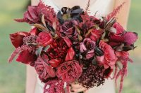 a bright fall wedding bouquet with black, marsala and red blooms, twigs, branches and neutral ribbons is a fantastic idea
