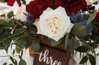 a bright wedding centerpiece of marsala, white blooms, eucalyptus and thistles is a lovely idea for a rustic wedding