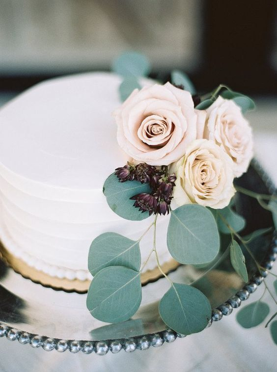 a buttercream-frosted wedding cake with roses and greenery is a very elegant and chic idea