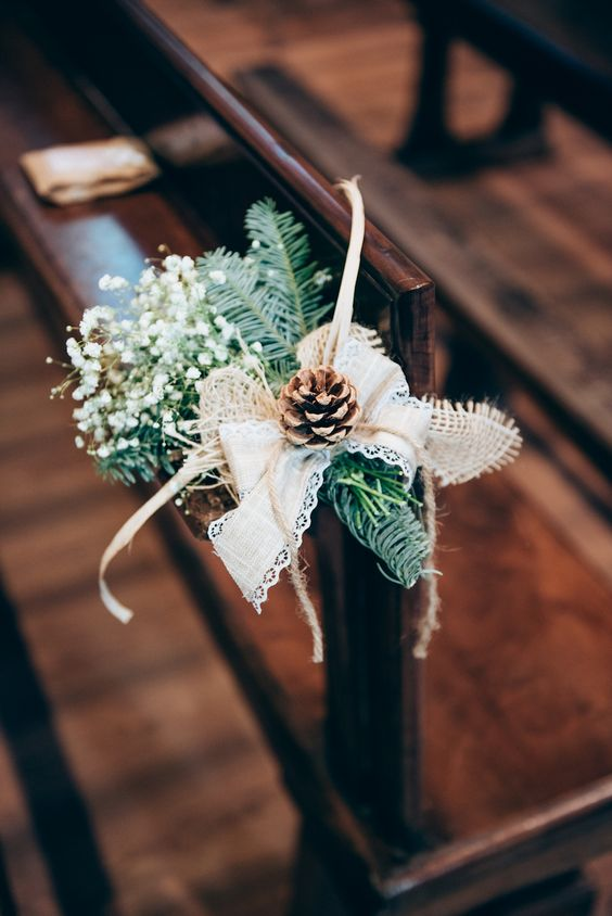 a chair posie of evergreens, a lace and burlap bow, a pinecone, baby's breath and some twine for a winter wedding aisle