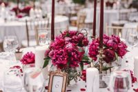 a chic and elegant wedding table with marsala blooms and candles, with petals and succulents plus a table number