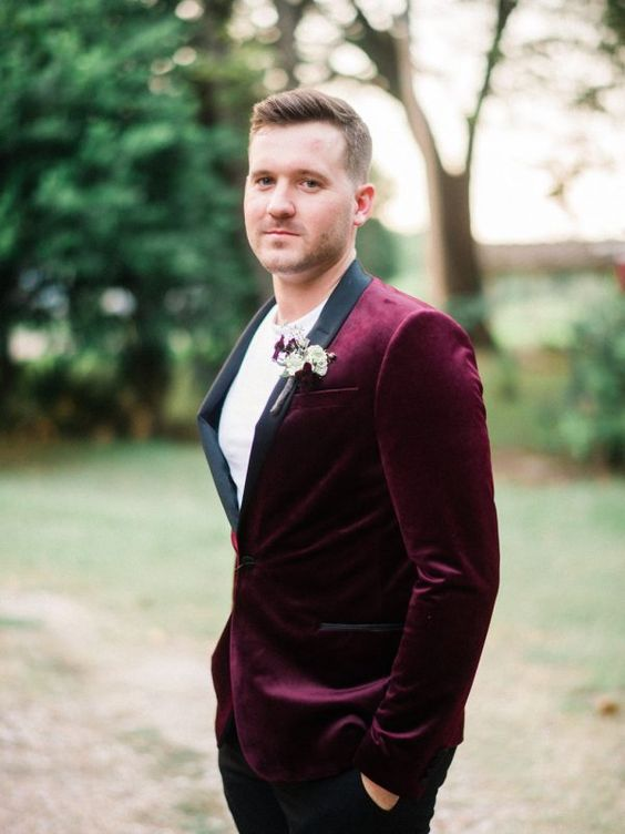a chic groom's look with a burgundy tux with black lapels and black pants calmed down with a white tee